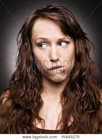 doubt. beautiful woman over dark background