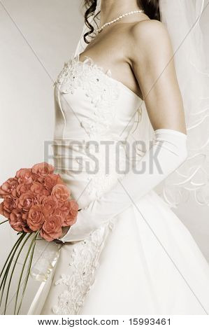 desaturated image of young woman in wedding dress with bunch of flowers