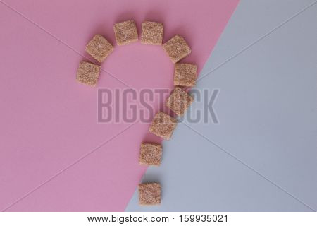 Brown sugar cubes shaped as a question mark on colourful background. Top view. Diet unhealty sweet addiction concept