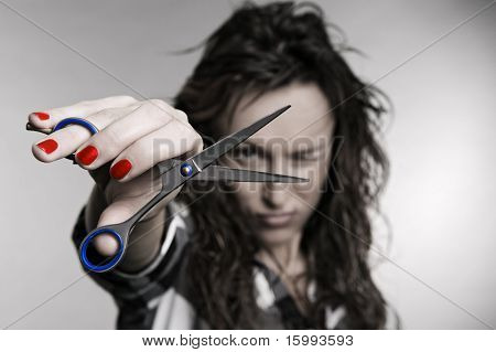 attractive hairdresser with scissors over grey background