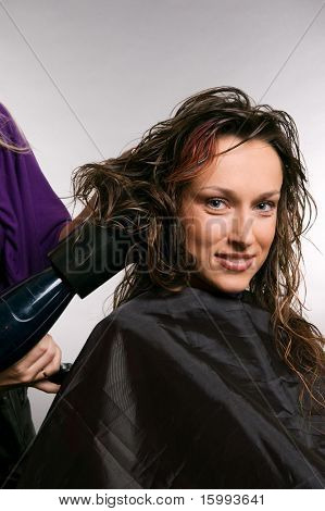 hairdresser blow-dry hair of client. studio shot over grey background
