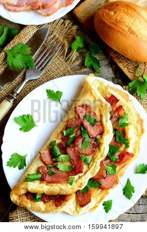 Delicious omelette on a plate. Omelette stuffed with fried bacon and decorated with chopped fresh parsley. Sliced bacon, bread, cutlery, fresh parsley leaves on wooden background. Top view. Closeup