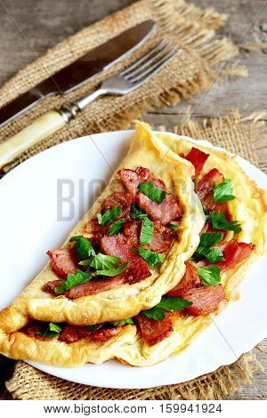 Cooked bacon omelet. Homemade spicy omelet with fried sliced bacon and parsley on a white plate, fork, knife on old wooden table. Very delicious eggs breakfast idea. Rustic style. Closeup