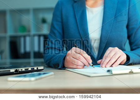 Female executive approves corporate business plan and signing document on office desk