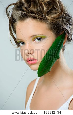 Beauty portrait of a young girl with bright green makeup and a fresh leaf on her face.