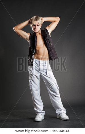 young dancer in white trousers posing over dark background