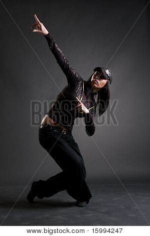 beautiful brunette dancing against dark background