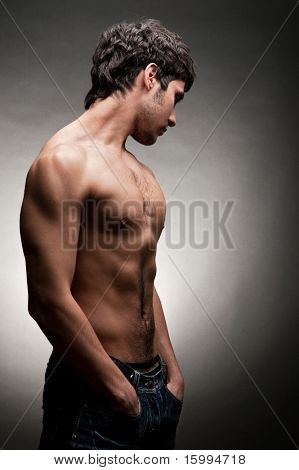 adult man with naked torso posing against dark background