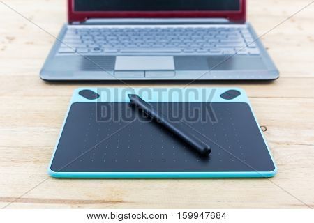 Digital graphic tablet and pen isolated on wood desk Background.