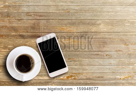 Smart phone with blank screen area and coffee cup on vintage wooden background.