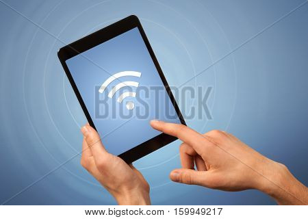 Female fingers touching tablet with wireless connection icon