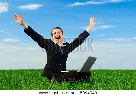 happy woman with laptop siting at the green grass
