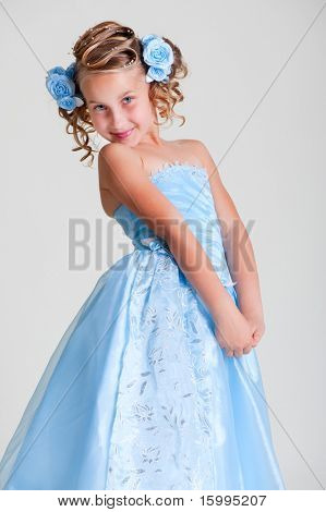 joyful little princess in blue dress posing against grey background