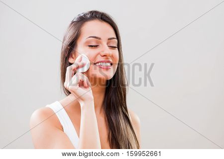 Portrait of young woman who is cleaning skin on her face.