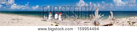 Panorama of happy beautiful family in red Santa hats on a tropical beach celebrating Christmas