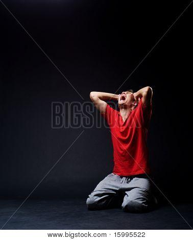 sorrowful man screaming in darkness