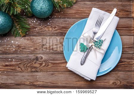 Christmas table place setting with blue plate, fork and knife, decorated ribbon and bow with fir-tree toy, white napkin and christmas pine branches with christmas balls. Christmas holidays background.