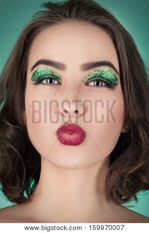 fun girl with bright cosmetcs on green background