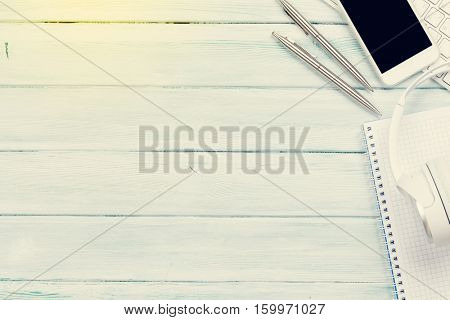 Headphones, phone and pc on wooden desk table. Music concept. Top view with copy space. Sunny toned