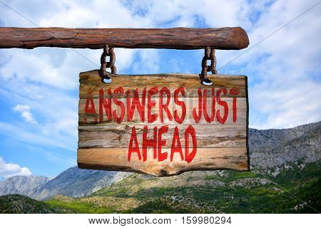 Answers just ahead motivational phrase sign on old wood with blurred background