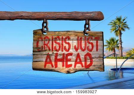 Crisis just ahead motivational phrase sign on old wood with blurred background