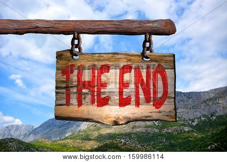 The end motivational phrase sign on old wood with blurred background