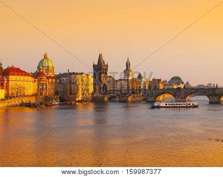 Prague Evening. Towers of Old Town and Charles Bridge over Vltava River illuminated by orange sunset. UNESCO World Heritage Site. Prague, capital city of Czech Republic, Europe