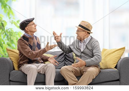Seniors sitting on a sofa and arguing with each other