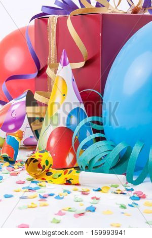 Birthday party with a gift or present box, party hats, horns or whistles, balloons, confetti and streamers
