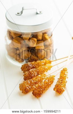 Brown amber sugar crystal on wooden stick and sugar cubes in jar.