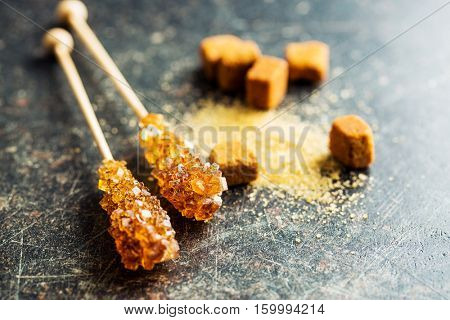 Brown amber sugar crystal on wooden stick and sugar cubes.