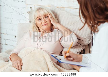 Help me to recover. Pleasant aged sad woman lying in bed and describing her disease while professional doctor sitting near her