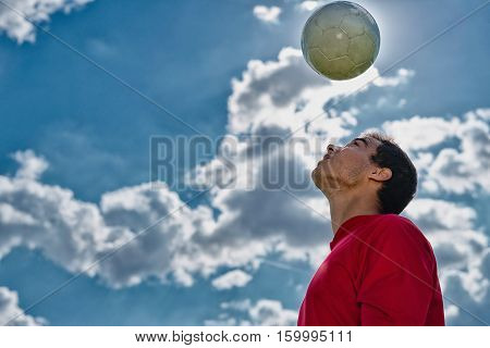 Soccer player bouncing ball, toned image, sky