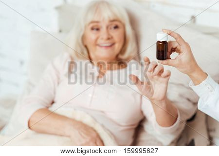 Magic remedy.Selective focus of bottle with pills in hands of professional doctor holding it and giving to a sick elederly woman