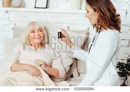 One pill per day. Positive ill aged woman lying in bed wile professioanl doctor vising her and giving remedy