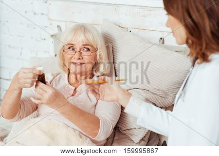 Improve your health. Pleasant sick elderly woman lying in bed and holding bottle with pills while professioanl doctor visiting her at home
