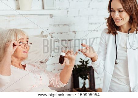 A piece of advice. Pleasant professioanl doctor advicing aged ill woman remedy and talking with her