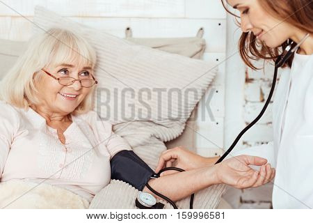Professional attitude. Pleasant sick delighted elderly woman lying in bed and smiling while professioanl measuring her blood pressure at home