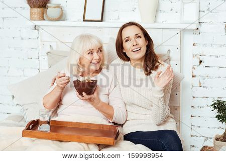Lively talk. Pleasant delighted woman lying in bed and enjoying breakfast while talkign with her beautiful caring granddaughter