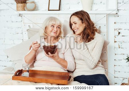 Share your emotions. Joyful delighted young woman sitting with near her grandmother in bed and talking while takigng care of her