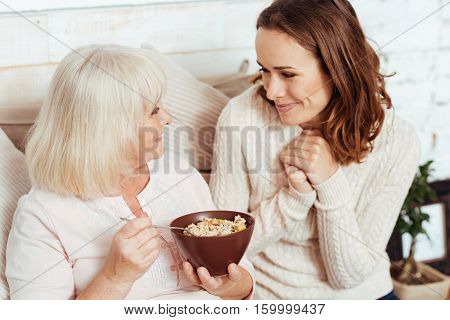 With love. Pleasant delighted elderly woamn lying in bed and eating outmeal while resting with her young beautiful granddaughter
