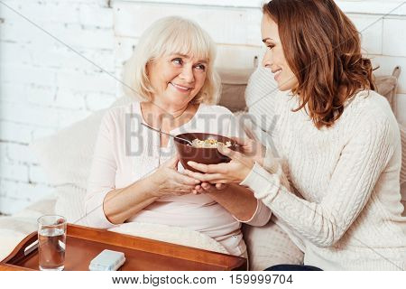 Warm relations. Positive delighted elderly woman lying in bed and having breakfast while her loving granddaughter takign care of her