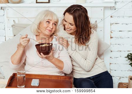 In an elated mood. Cheerful content elderly woman lying in bed and having breakfast while her carign young granddaughter sitting nearby
