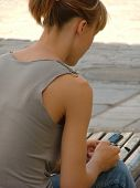 image of teen pony tail  - pretty girl playing with her mobile phone - JPG