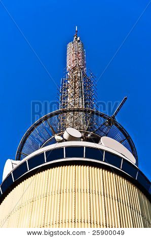Telecom Tower With Microwave Links And Cellular Network Antennas On Blue Background