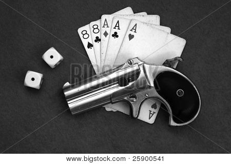 "Circa 1889, Model 95, Type II Model 3 Double Derringer on card table with aces and eights aka a ""Dead Mans Hand"" and dice showing ""snake eyes"" in black and white"