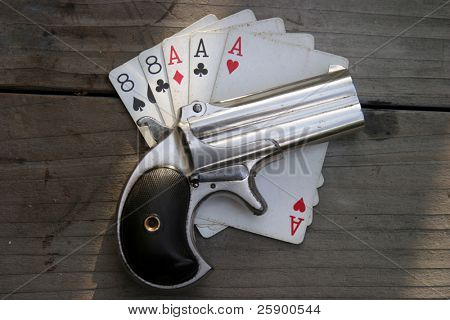 "Circa 1889, Model 95, Type II Model 3 Double Derringer, on antique wooden table aces and eights aka a ""dead mans hand"""