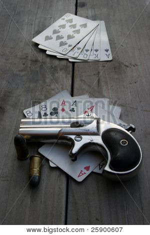 Circa 1889, Model 95, Type II Model 3 Double Derringer, on an antique wooden table with aces and eights aka a