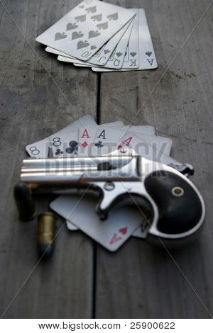 """Circa 1889, Model 95, Type II Model 3 Double Derringer, on an antique wooden table with aces and eights aka a """"dead mans hand"""""""