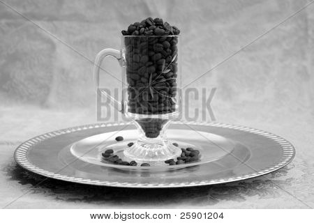 Glass coffee mug filled with unground coffee beans on a gold background (in black and white)